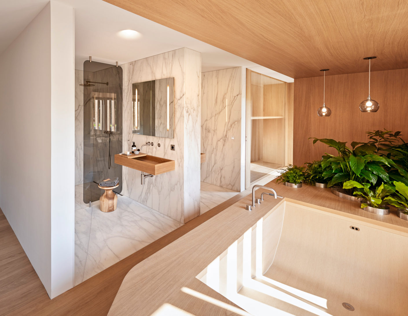 Reduced shapes and a lot of wood as a material provide an optical rest in the open bathroom concept.