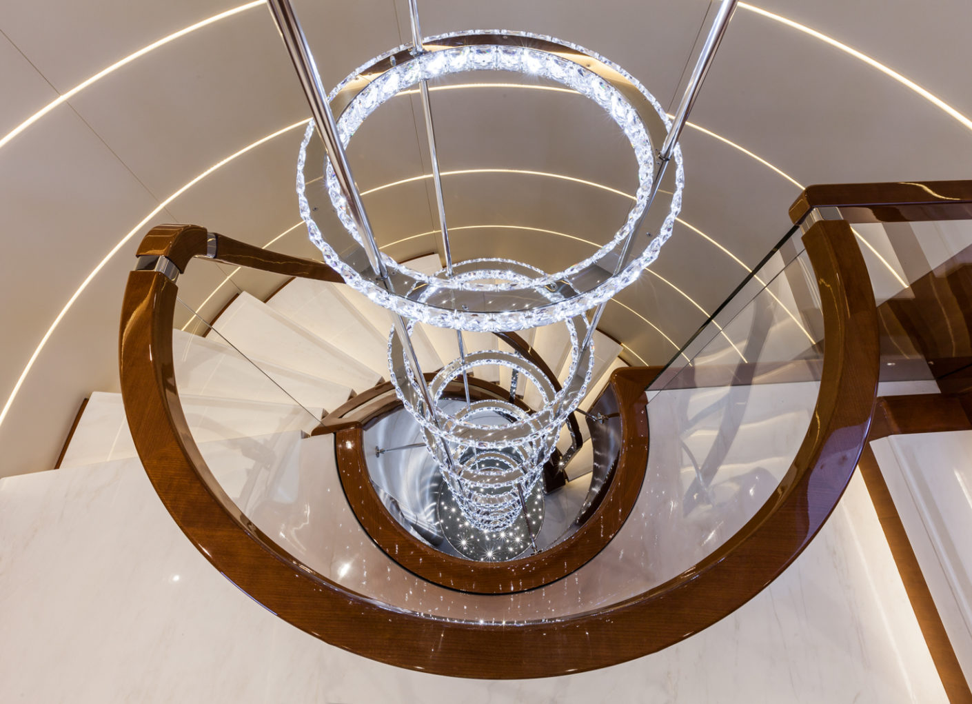 The steel rings studded with Swarovski crystals provide a decorative light sculpture for the spiral-shaped staircase connecting the lower to the upper deck.