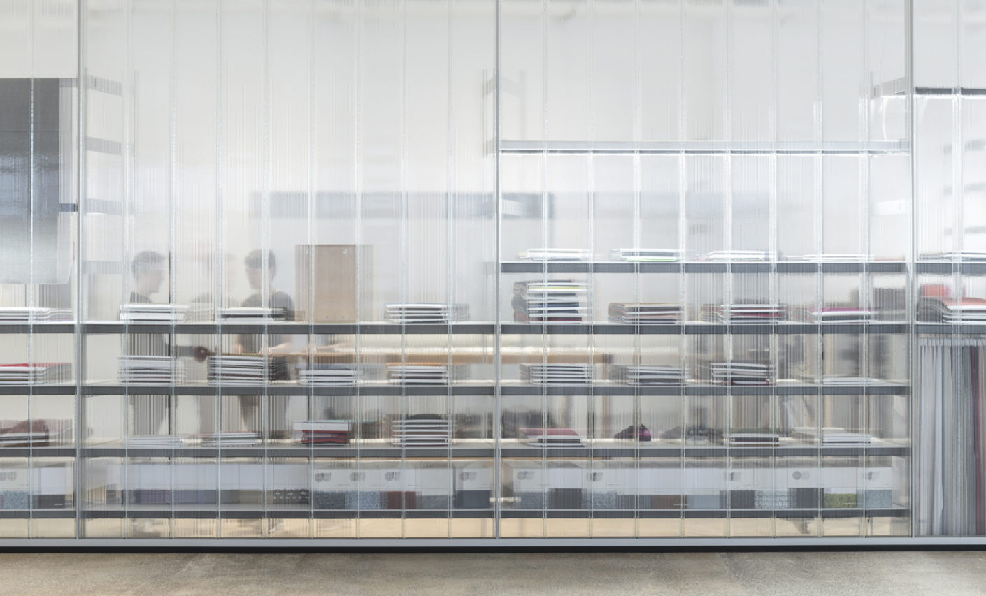 The transparent glass screens effectively separate the offices from the warehouse spaces and presentation areas for products.