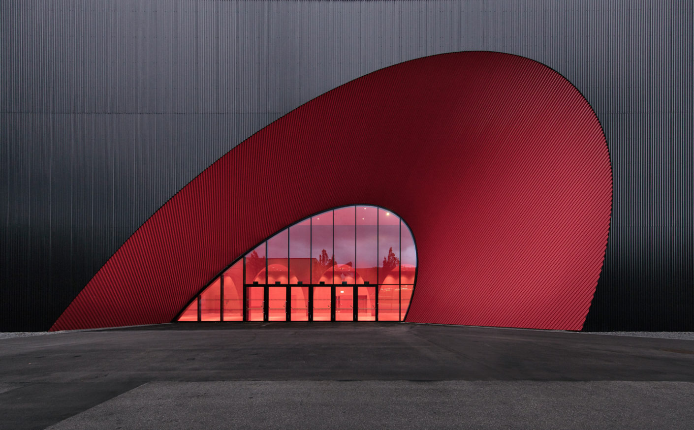 "The conical section in its intense crimson red, the ""trade-fair red"" of Messe Dornbirn, creates a zestful contrast to the rectangular building's black exterior."