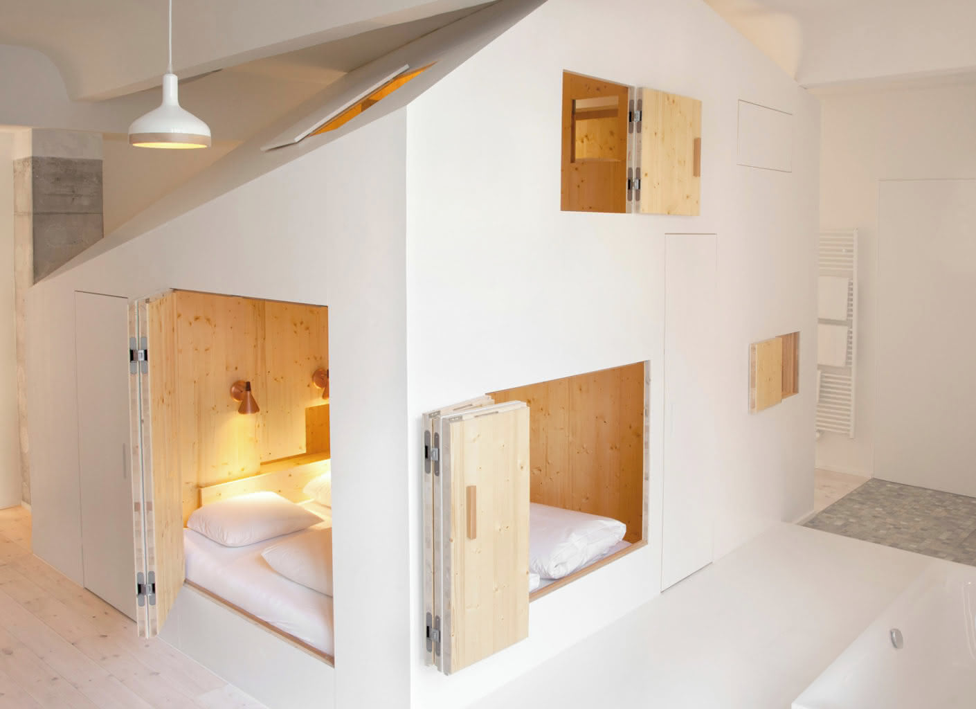 The danish architect Siguard Larsson inserted a two-storey living cube into two rooms of the hotel Michelberger.