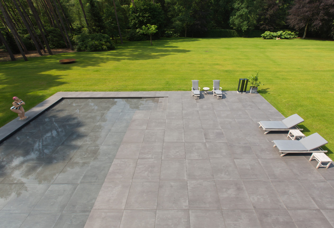"The spacious dark-grey patio with tiles out of the ""Ultragres Terra Maastricht""-collection by Mosa, embracing the house like an artificial topographical band and sloping slightly to an expanse of water."
