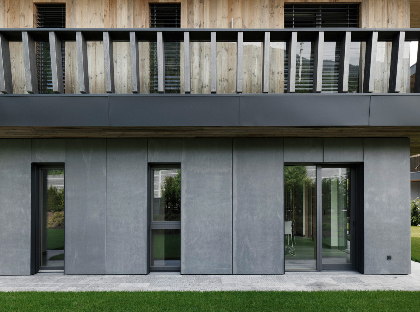 While the upper stories are clad in wood, the ground floor relies on anthracite-colored panels made of fibreC, fiberglass concrete.
