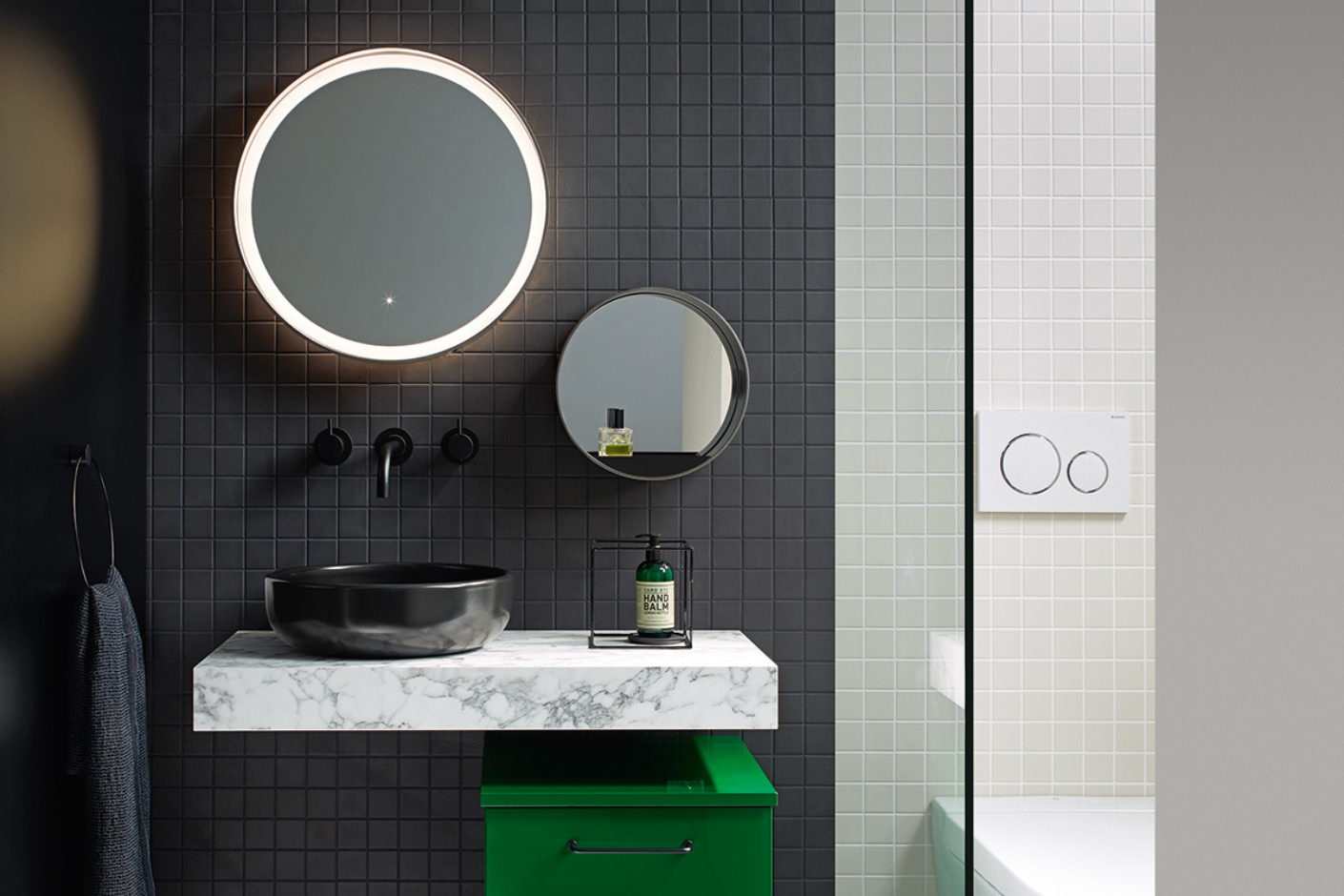 Bathroom with gray tiles, black washbasin and vanity unit in bold green