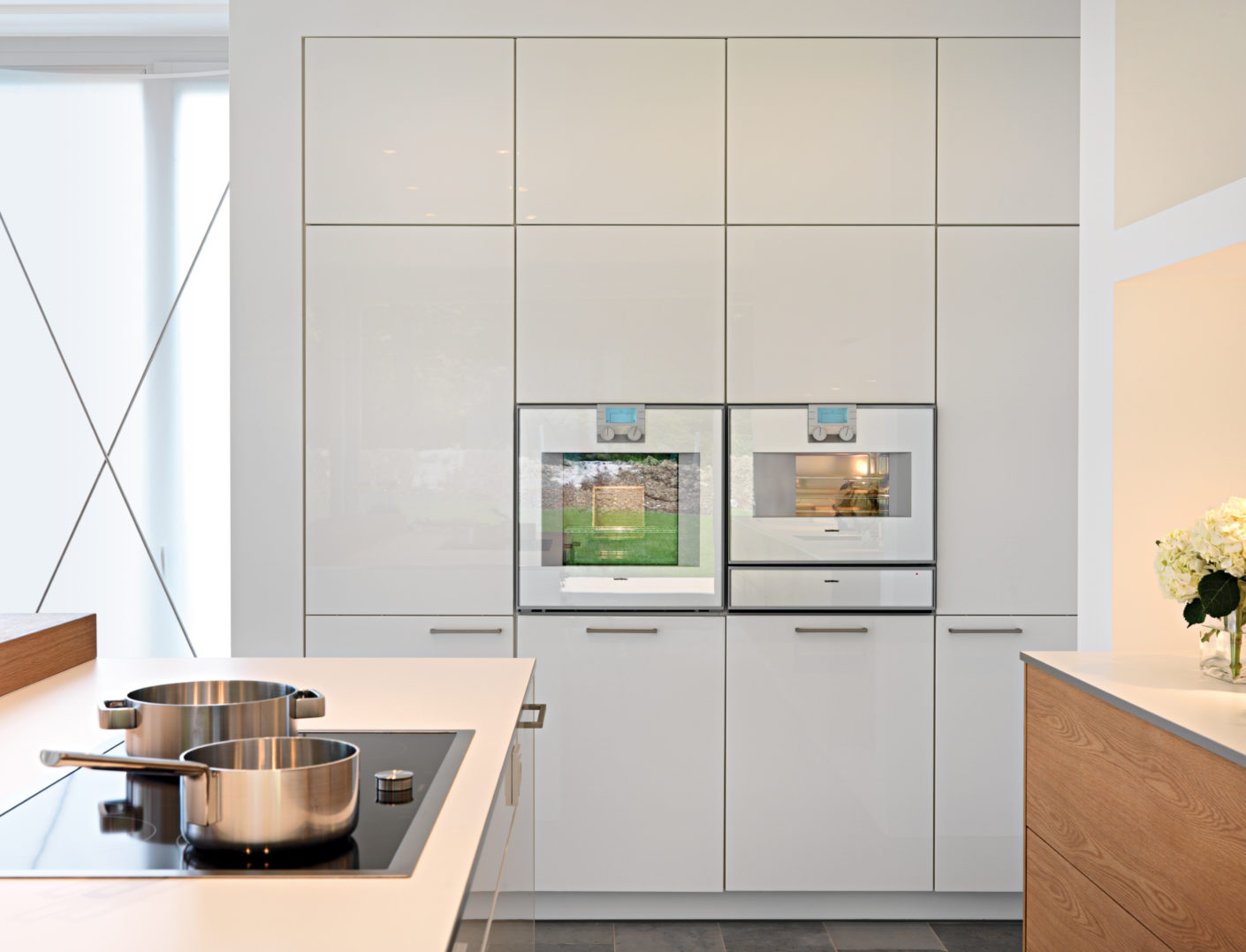 All the electrical appliances are installed flush into the upper row of fitted cupboards or embedded in the masonry to form the kitchen island and create an ergonomic worktop.