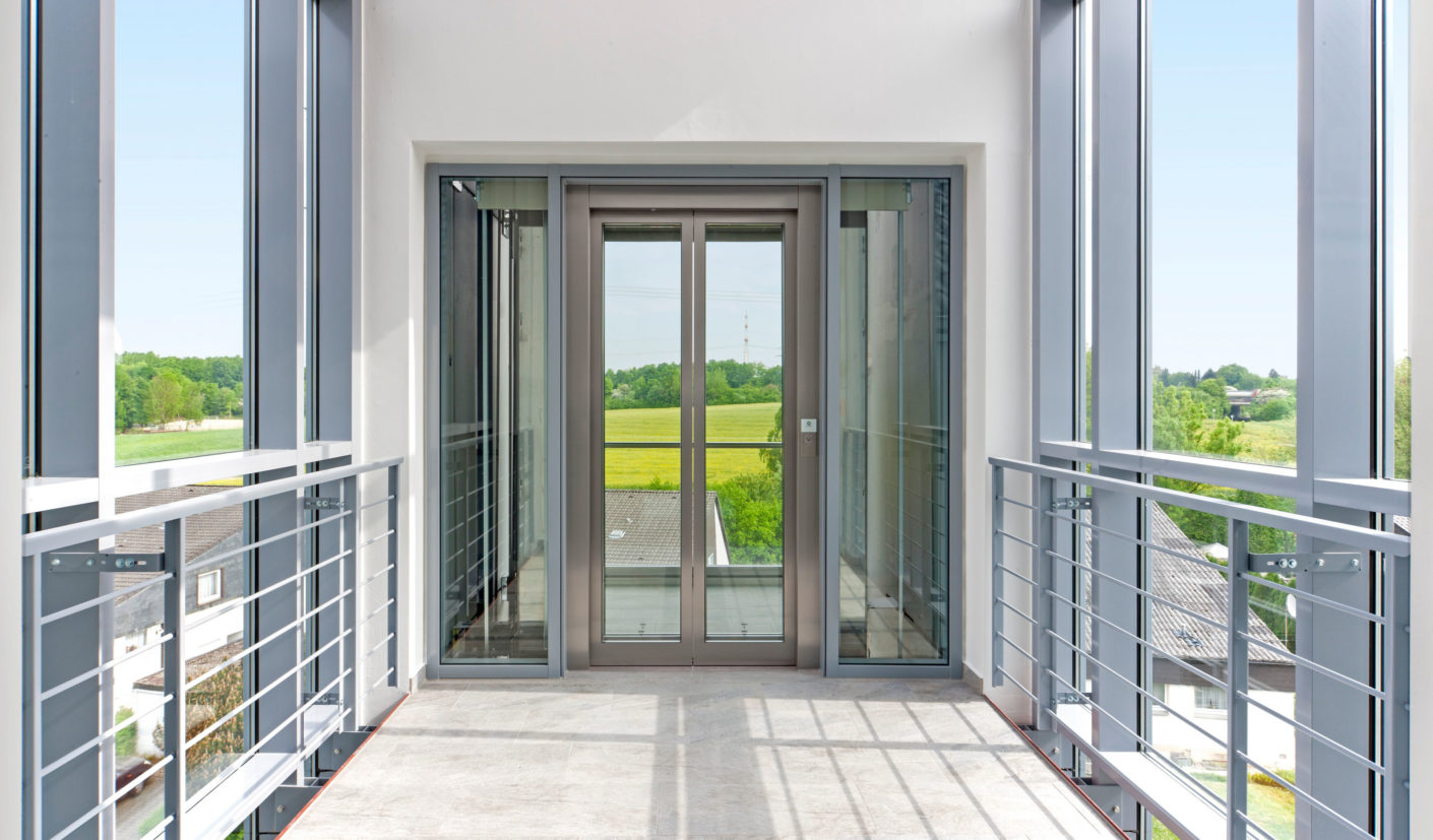 A small air bridge in the new structure leads to the glazed elevator. Thanks to the transparent front tenants enjoy a panoramic view from the upper floors.