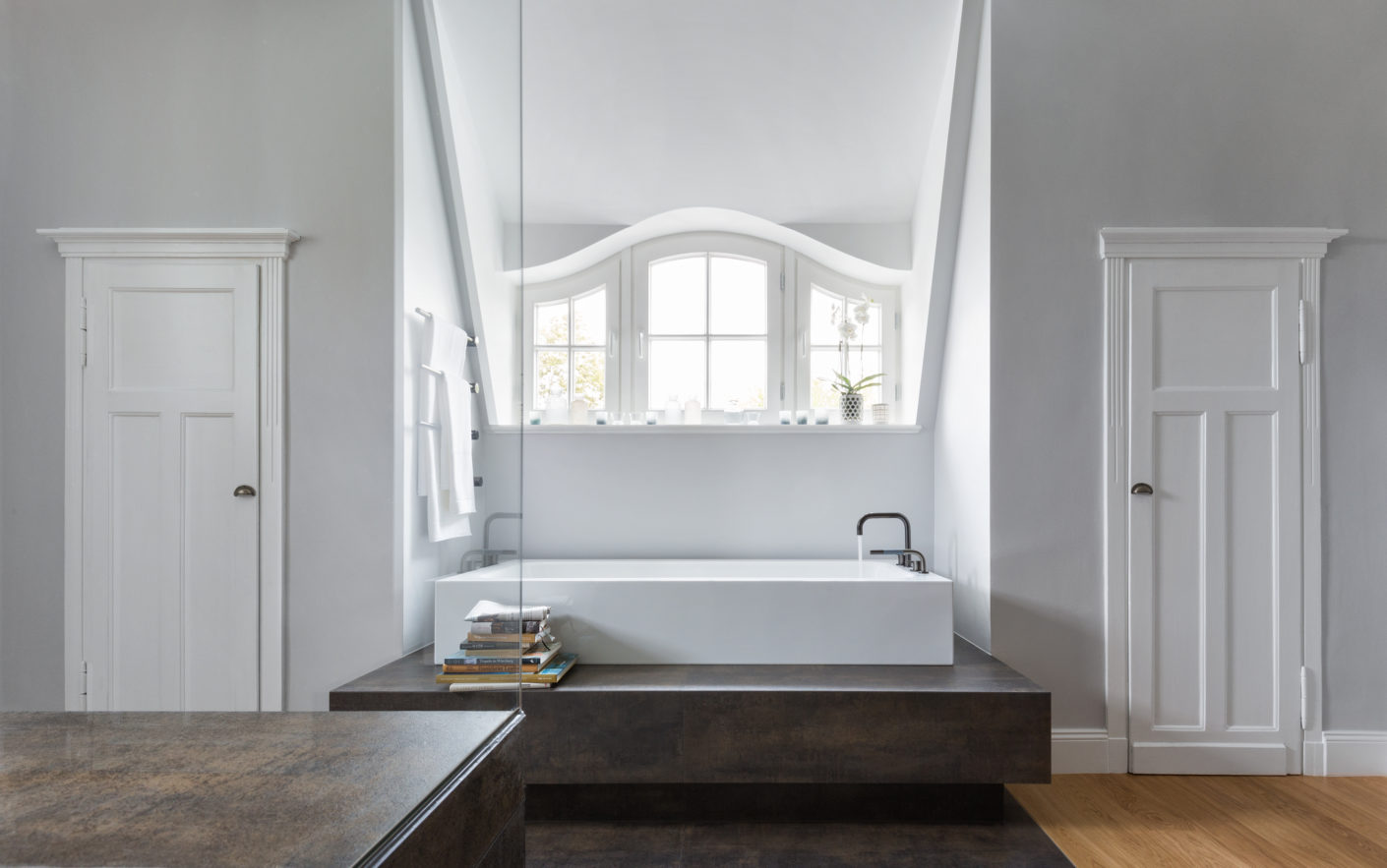 The bathroom is now a bright room which, with its beautiful dormer windows and doors still brings the original building to mind, but is otherwise awash in modern life.