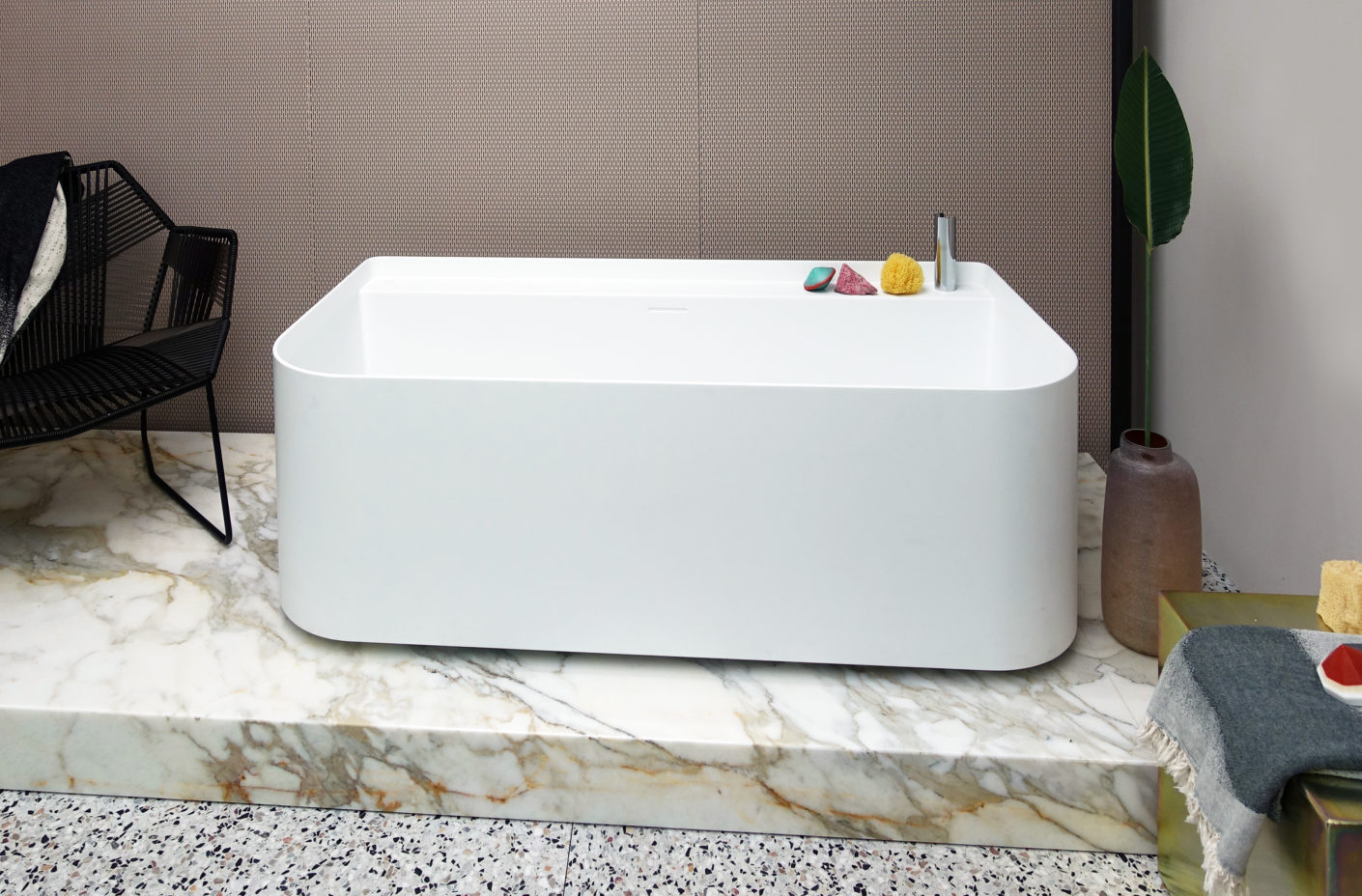 Functional and sculptural: Patricia Urquiola puts the bath on a marble base while running, and offers a built-in tray for sponge and soap.