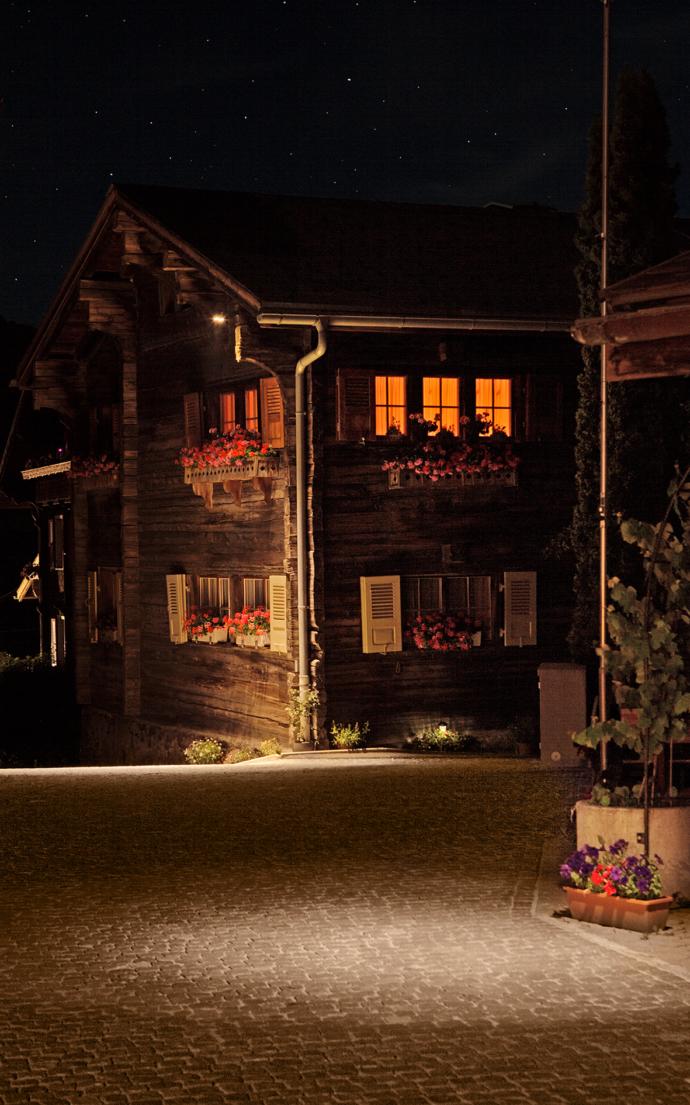 In warmen Licht getauchtes Schweizer Dorf bei Nacht