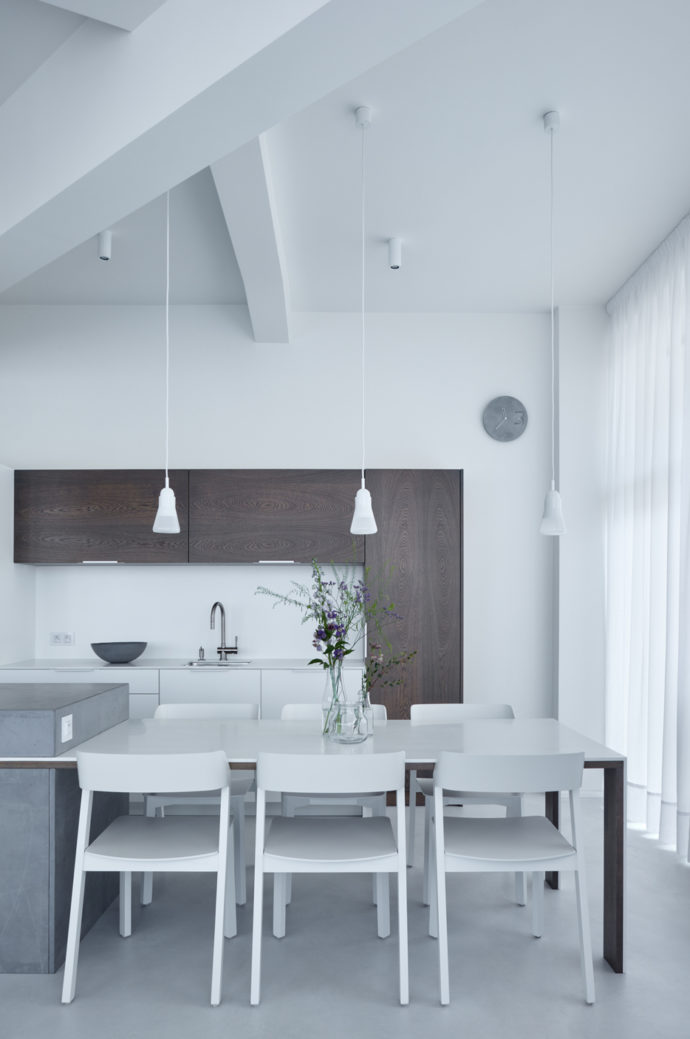 """A white table top made of the Corian mineral material connects to the kitchen island and is served by six white """"Merano"""" chairs from clay to the dining table."""