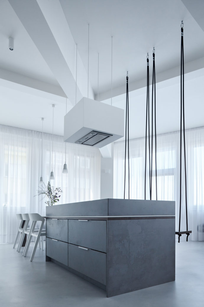 Klára Valová from Studio SMLXL decided to use a kitchen island made of gray stained wood for the open-plan living room.