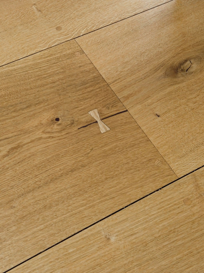 The natural cracks in the oak planks have been preserved and are fixed with loop-shaped inserts.