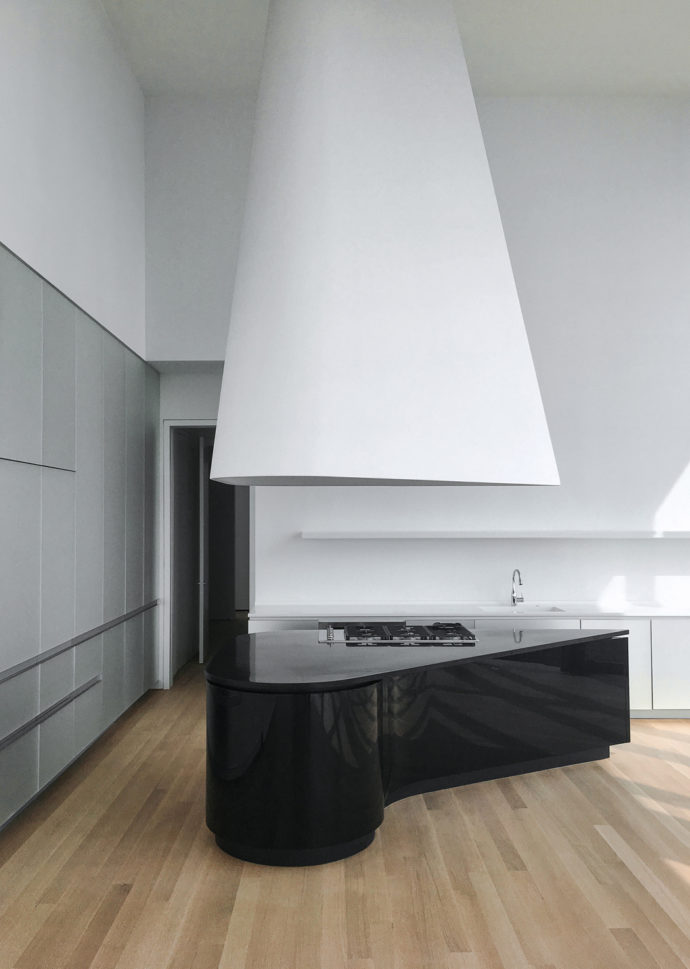 With their fluid shapes the glossy black kitchen blocks with granite countertops fit the layout of the space perfectly.