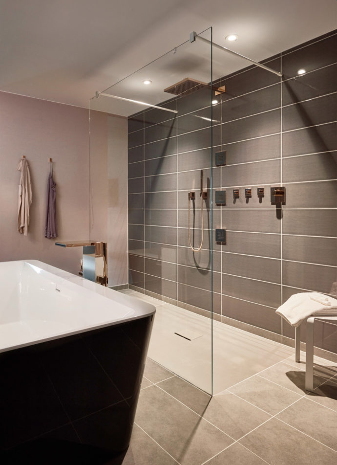 Soft-nude surfaces create a pleasant atmosphere in the bathroom in combination with matt gray tones and rich black.