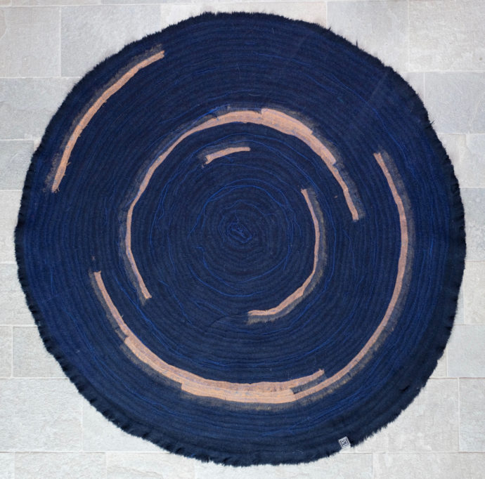 "The ""Deep Blue 01"" rug has a diameter of 230 cm and adds color highlights in cognac."