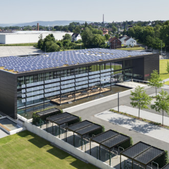 The energy-plus building, spanning nearly 4,000 square meters, has been furnished with a facade made from anodized sheet steel panels. Photovoltaic modules produce electricity regeneratively – the energy surplus is fed into the public network or used to charge electric cars or bikes.