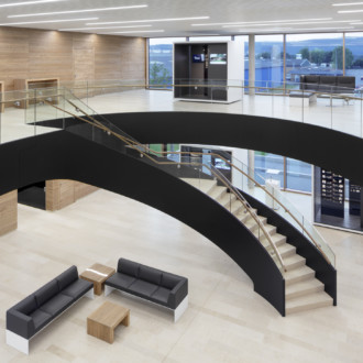 Sweeping lines: A curved staircase leads up to the higher floor from the foyer. The entrance area provides many oportunities for encounters and communication.