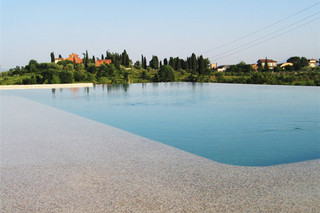 Beach overflow swimming pool coated in stone  by  Indalo Piscine