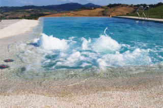 Beach overflow swimming pool covered with natural stone  by  Indalo Piscine