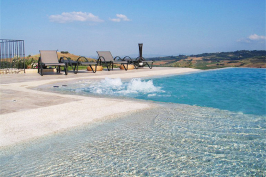 Strand Überlaufschwimmbecken beschichtet mit Naturstein