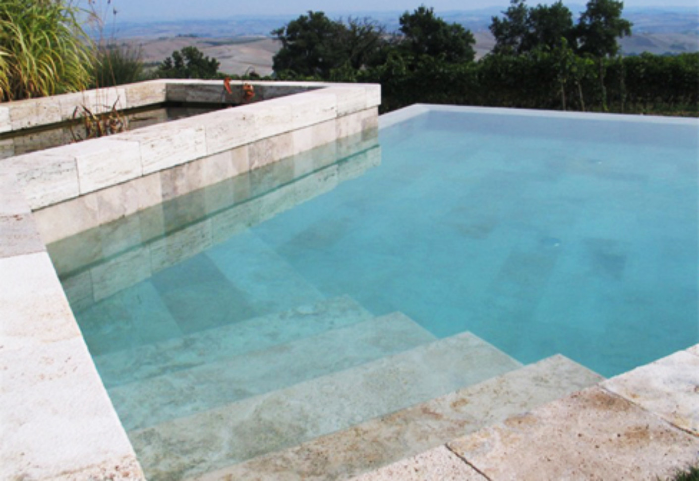 Overflow swimming pool coated in brown stone by indalo for Swimming pool manufacturers