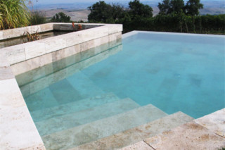 Overflow swimming pool coated in brown stone  by  Indalo Piscine