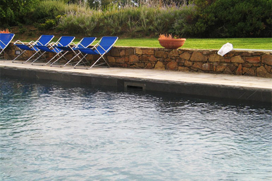 Swimming pool skimmer coated with natural stone